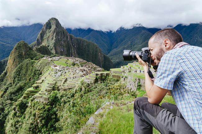 Hombre tomando fotos de Machu Picchu ciudadela y Huayna Picchu montaña, Perú - foto de stock