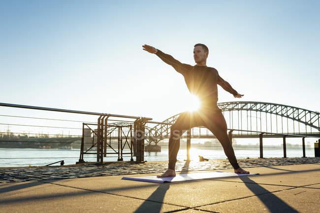 Німеччина, Кельн, молода людина практикуючі йогу в Ріверсайд — стокове фото