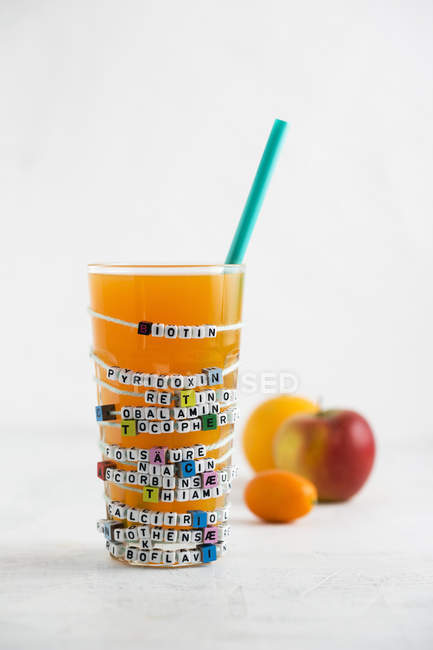 Multivitamin juice in glass with ingredients on white background — Stock Photo