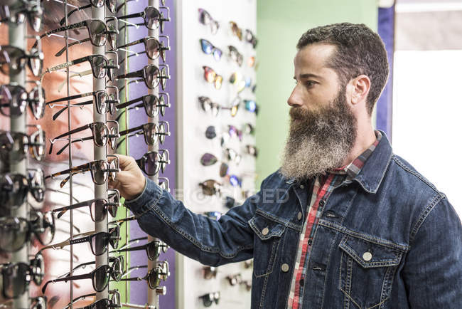Man choosing glasses in optical store — Stock Photo