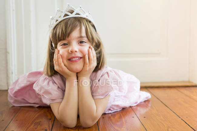 Portrait of smiling girl dressed up as a princess lying on wooden floor — Stock Photo