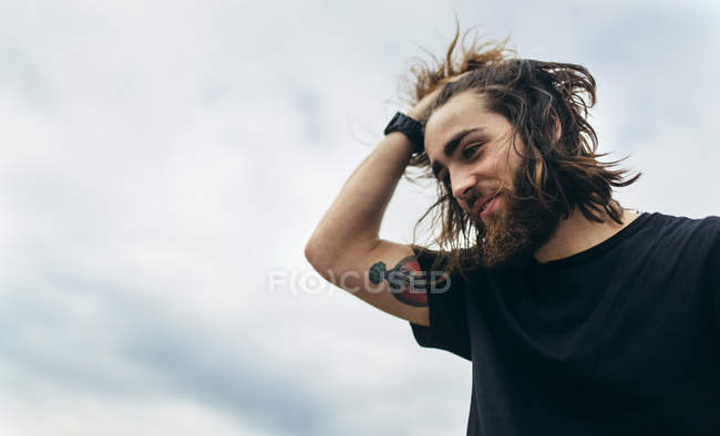 Портрет бородатого молодого человека с татуировкой на плече — стоковое фото