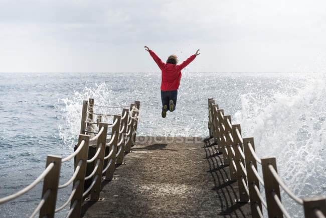Young woman jumping on pier at daytime — Stock Photo