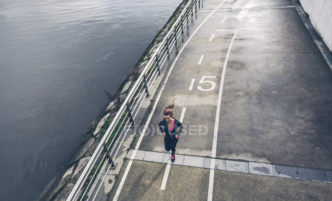 Woman running on waterfront road — Stock Photo