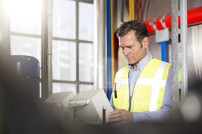 Man wearing reflective vest looking at device in industrial plant — Stock Photo