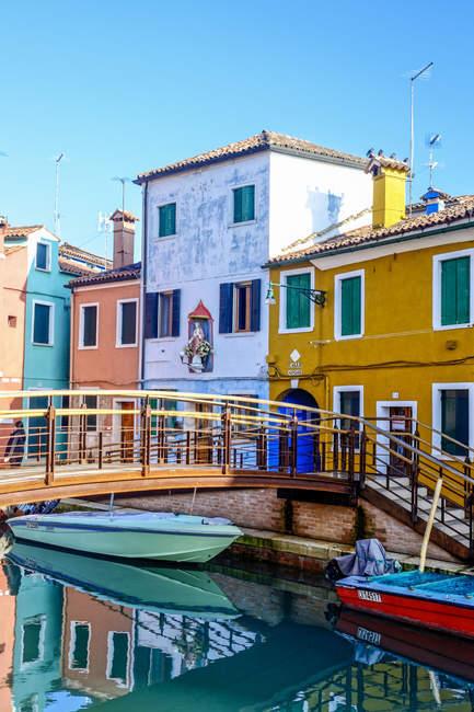 Italie, Vénétie, Burano, vue sur une ligne colorée de maisons avec passerelle au premier plan — Photo de stock