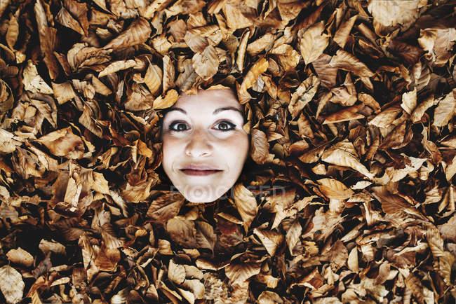 Frauengesicht zwischen Herbstblättern — Stockfoto
