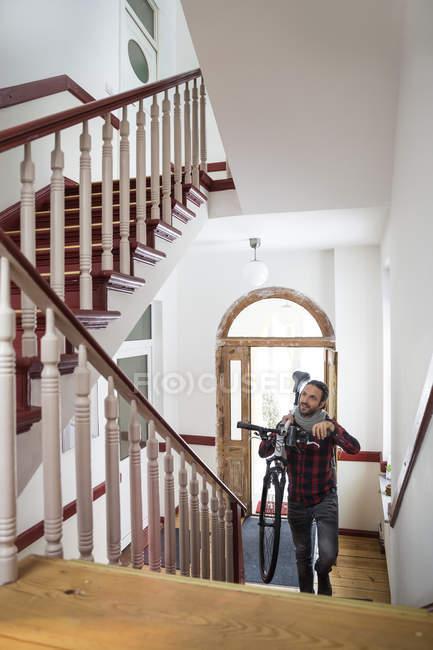 Mann trägt Fahrrad im Treppenhaus — Stockfoto