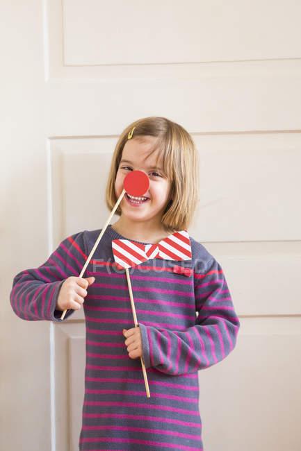 Ritratto di bambina con fiocco giocattolo e naso rosso — Foto stock