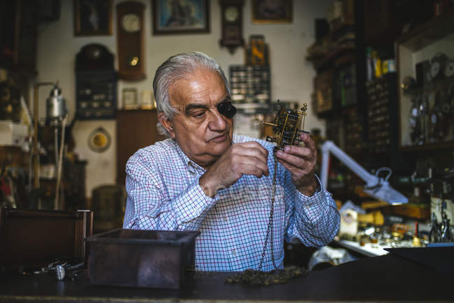 Watchmaker with okular working with an old watch — Stock Photo