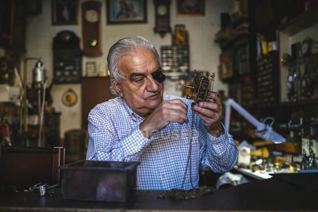 Часовщик с okular, работающих с старые часы — стоковое фото