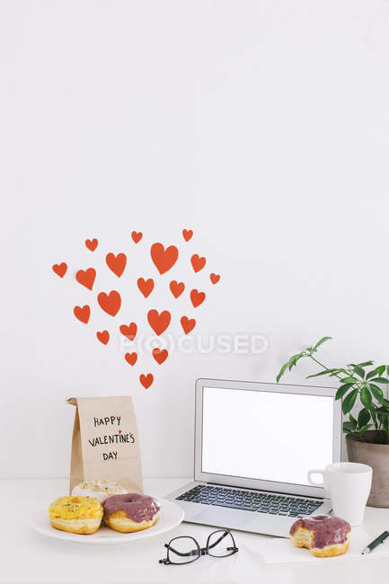 Still life with laptop, donuts, Valentine's day present and hearts on wall — Stock Photo