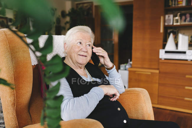 Portrait of smiling senior woman telephoning with smartphone at home — Stock Photo