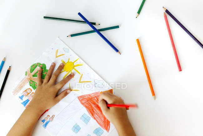 Hands of little girl painting with coloured pencils — Stock Photo
