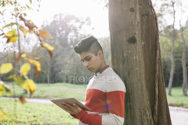 Joven apoyado en tronco de árbol mirando tableta digital - foto de stock