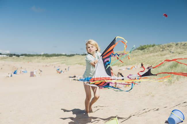 Blond boy holding flying kite on beach — Stock Photo