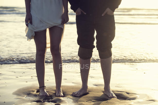 Legs of young couple standing barefoot atseafront — Stock Photo
