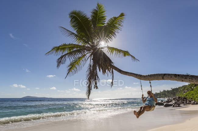 Seychelles, La Digue, Anse Fourmis, beach with palm and tourist on swing — Stock Photo