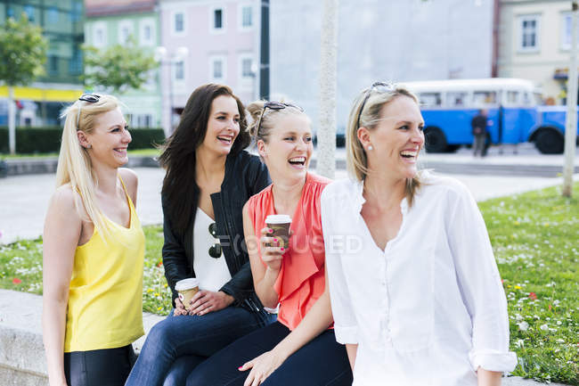 Four young women laughing outdoors turning round — Stock Photo