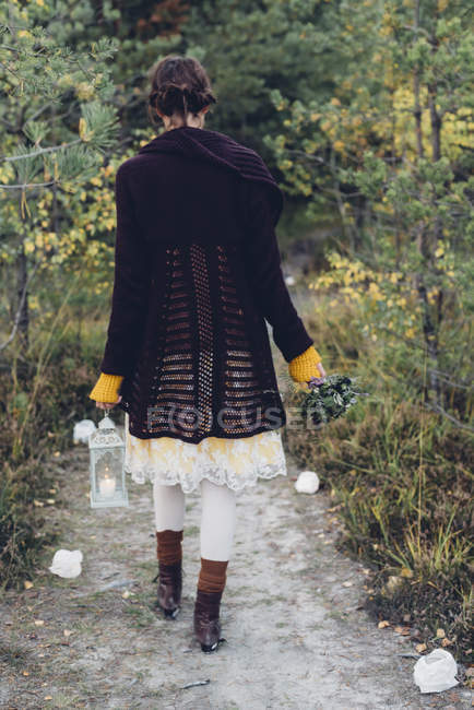 Back view of old-fashioned styled woman with storm lamp walking on a path — Stock Photo