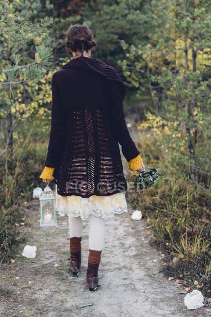 Задньої зору старомодним стилі жінка з лампою буря, ходьба на контурі — стокове фото