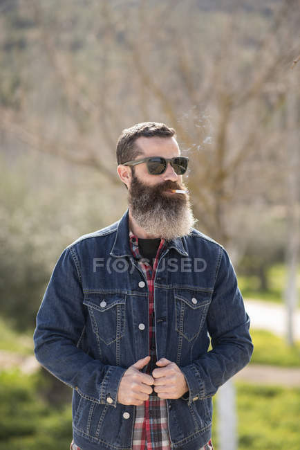 Bearded man smoking in park — Stock Photo