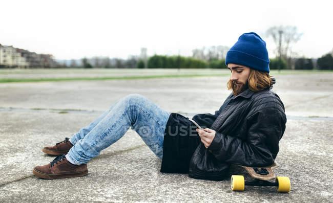 Молодий Скейтбордист, сидячи на землі, дивлячись на свій смартфон — стокове фото