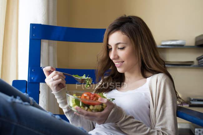 Молодая женщина ест салат в гостиной — стоковое фото