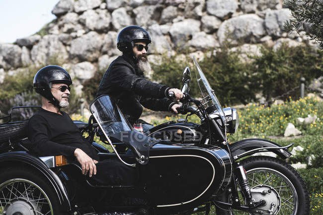 Portrait of two bikers standing with sidecar motorcycle on a meadow — Stock Photo