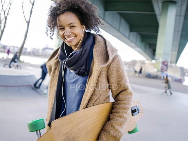 Lächelnde junge Frau mit Longboard hört Musik mit Kopfhörern — Stockfoto