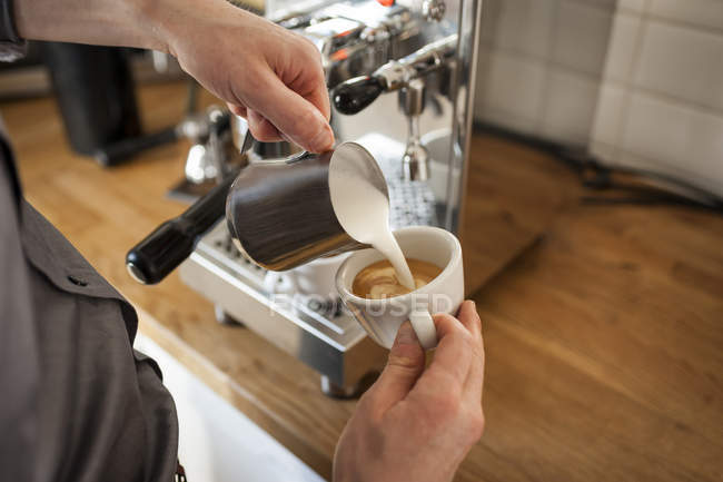 Close-up of male hands pouring milk froth in coffee cup — Stock Photo