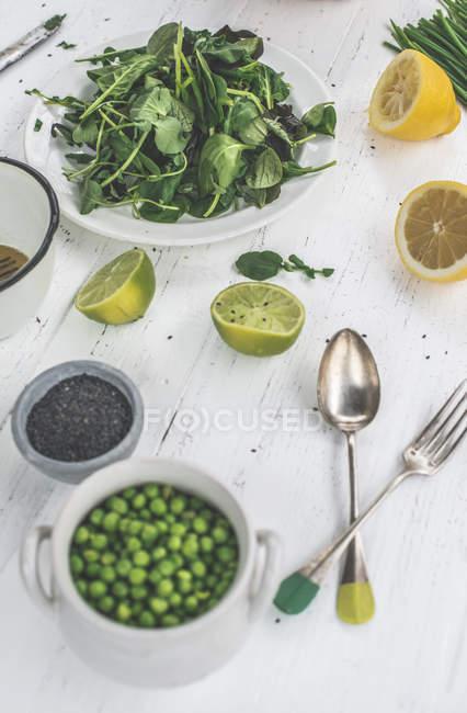 Zubereitung Salat mit Erbsen, Baby-Spinat, Brunnenkresse, Schnittlauch und schwarzem Sesam Dressing aus Kalk und Sesamöl — Stockfoto