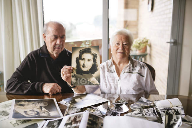 Senior woman showing an old picture of herself — Stock Photo