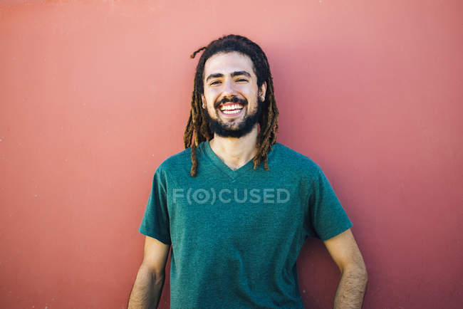 Portrait of laughing young man with dreadlocks and beard in front of a red wall — Stock Photo