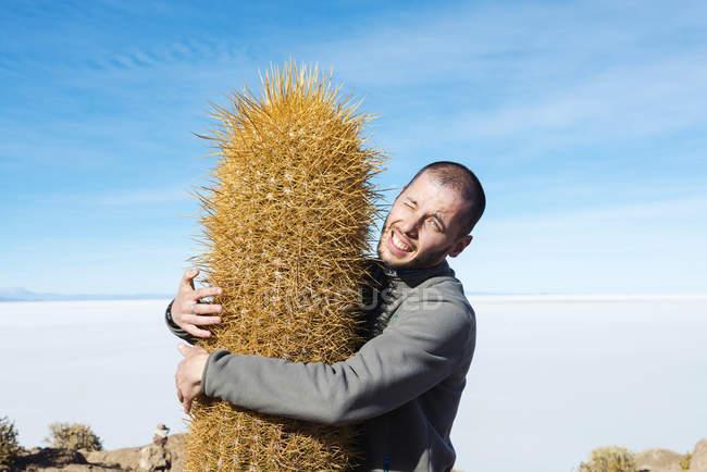 Bolivia, Atacama, Altiplano, Salar de Uyuni, man embracing cactus — Stock Photo