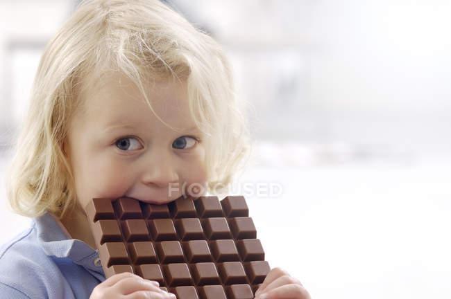 Portrait de petite fille blonde avec barre de chocolat — Photo de stock