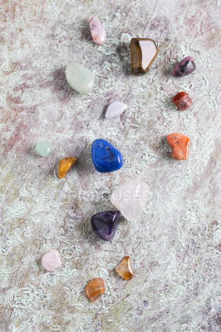 Diverse pietre semipreziose su superficie grigia — Foto stock