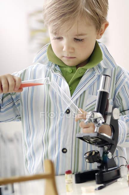 Портрет маленький хлопчик з пробірки і мікроскоп — стокове фото