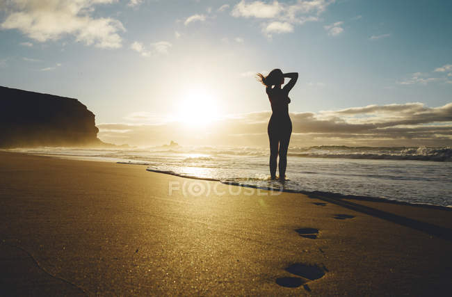 Woman standing on the beach at sunset — Stock Photo