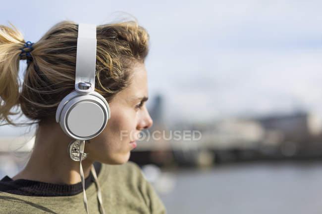Primer plano de la mujer escuchando música con auriculares - foto de stock