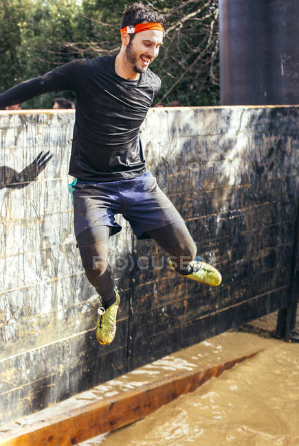 Participante en extrema carrera de obstáculo saltando sobre la pared - foto de stock