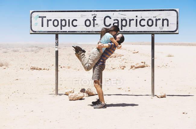 Namibia, namib wüste, swakopmund, reisendes paar küsst sich neben dem zeichen des capricorn — Stockfoto