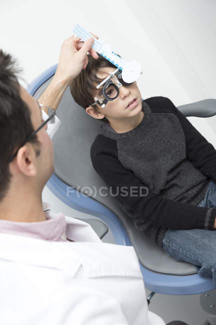 Optometrist examining eyesight of boy in clinic — Stock Photo