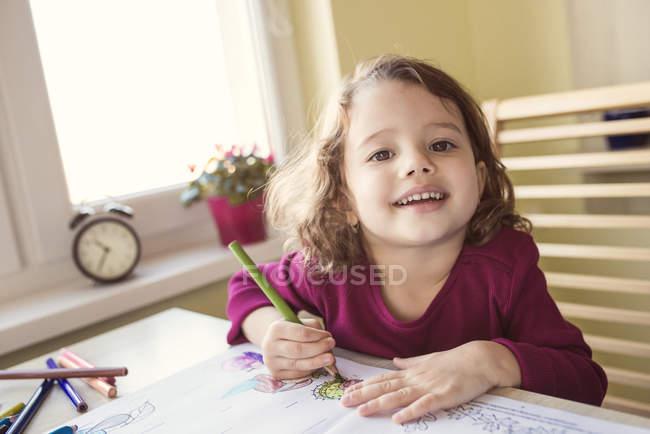 Retrato de niña sonriente pintando con lápices de colores - foto de stock