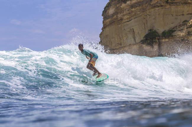 Indonesia, Lombok, surfer on a wave near rock in ocean — Stock Photo