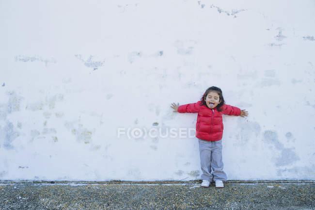 Porträt von kleinen Mädchen mit ausgestreckten Armen Zunge gelehnt — Stockfoto