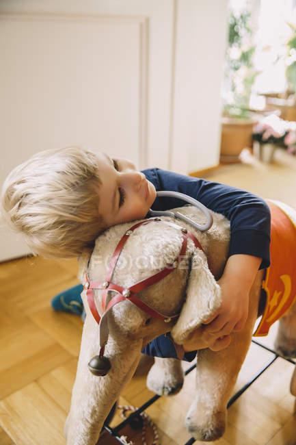 Boy hugging old plush elephant at home — Stock Photo