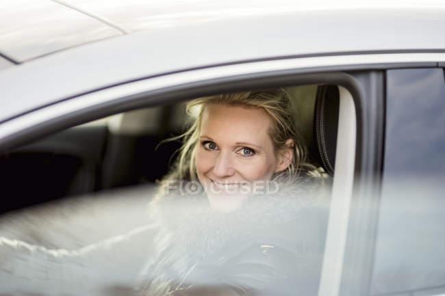 Donna in macchina sorridente — Foto stock