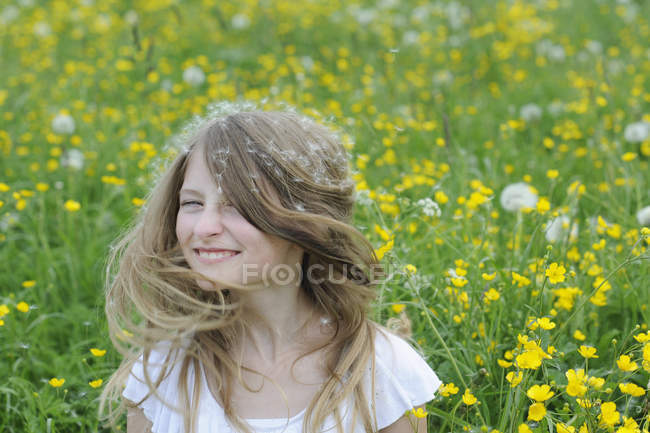 Portrait de fille souriante avec des graines de pissenlit sur ses cheveux — Photo de stock