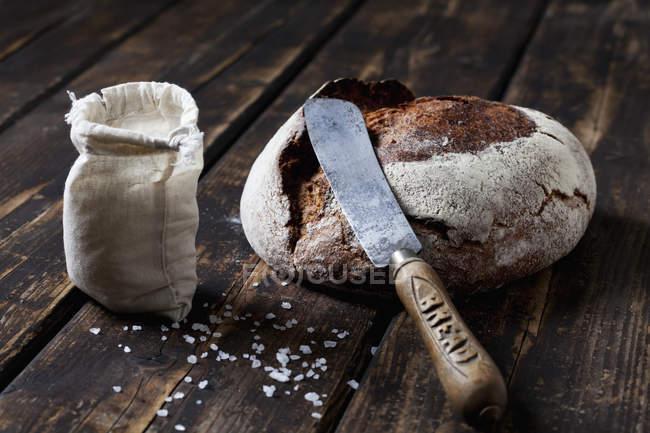 Pain croustillant avec couteau et grains de sel — Photo de stock